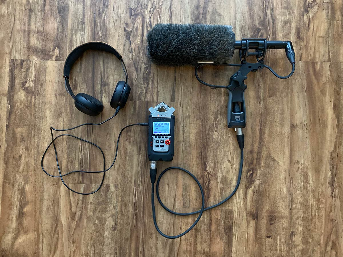 a photo of headphones, recording device, and shotgun microphone in handgrip
